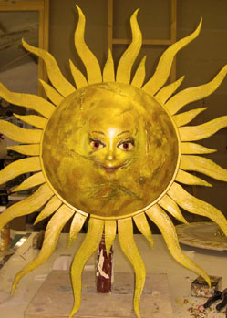music video gold prop sun head